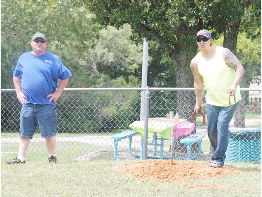 Jim Hancock of Nocona looks on as Dustin Sutton of Bowie pitches at the horseshoe pitching tournament in Pelham Park on Saturday. Hancock won the singles competition later during the event. Read the mid-week edition of The Bowie News for more. (News photo by Eric Viccaro)
