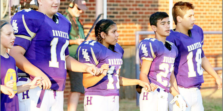 Patrick Johnston/Times Record News Harrold's Hunter Edwards (from left), Olivia Perez, Mark White and Kastin Grantham participate in the school fight song before their game against Moran on Sept. 2 in Harrold.