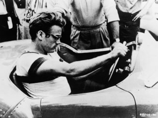 American actor James Dean (1931 - 1955) sits behind the wheel of a sportscar in a still from the documentary movie 'The James Dean Story,' directed by Robert Altman and George W. George, 1957. (Photo by Warner Bros. courtesy of Getty Images)