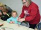 Library Director Beth Hiatt shows a child how to make a jingle bell craft during Wednesday's weekly storytime at the Bowie Library. During weekly storytime this past week Mrs. Claus visited to read stories to the children.