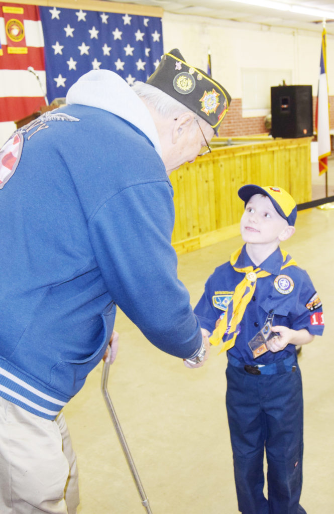Cub Scout David Rose shakes hands with Jerry Coley, a Korean War veteran during Saturday's 70th anniversary open house at the Bowie Veterans of Foreign Wars Post No. 8789. The scouts opened the program with the posting of colors and the pledge of allegiance.